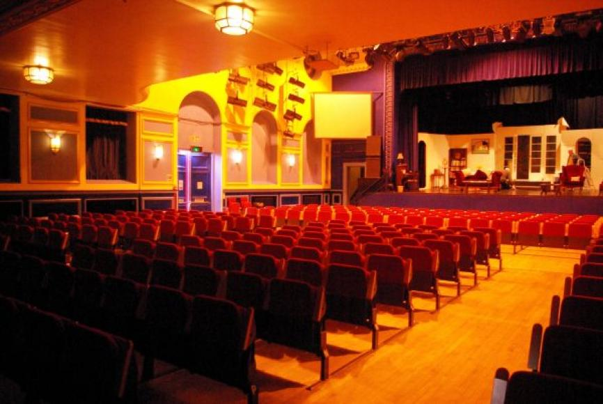 keywords interior auditorium stalls flat floor lighting bar chairs proscenium stage aisle purple yellow red & Auditorium at the Shanklin Theatre Isle of Wight 2014 | Theatres Trust